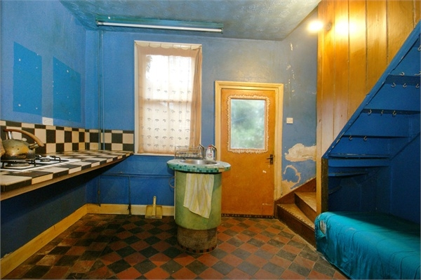 The sink is in the middle of the room, next to the back door.  The stairs are bizzarre, and if there were ever a house fire, the occupants would not be able to get out.  Also the walls are filthy.  You have to admire the optimism of the estate agent - this beaut was listed at around £80,000 in York.